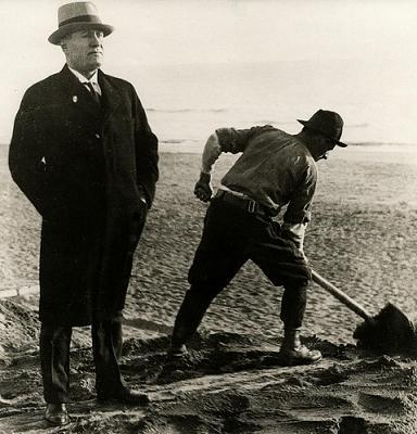 Een dag uit het leven van Mussolini: Benito Mussolini in zijn karakteristieke trotse  houding met een spittende arbeider op het strand van de badplaats Ostia bij Rome. Foto uit 1931.